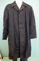 Image of 2015.025.032 - US Air Force Regulation Rain Coat, c. 1950-1982.  Dark blue nylon/rayon long raincoat has a three-hidden-button closure, long sleeves, a split at center back bottom below waist, epaulet straps secured with buttons beneath notched collar, small flaps with buttons at wrists and two large pockets at waist with vertical side openings.