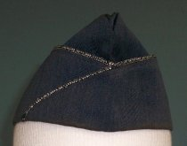 """Image of 2015.025.044 - US Air Force Uniform Garrison Cap, c. 1950-1982.  Blue-colored wool rectangular cap has a 2.75"""" folded cuff at bottom, the top edge of which has black and silver decorative cording.  The cuff overlaps at an angle on the proper right side.  Interior appears to be lined with light gray-colored rayon and there is a brown-colored leather band around interior bottom to lend support."""