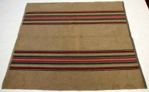 "Image of 0002.327 - Woven Wool Throw Rug, n.d.  Warp is comprised of dark tan 1/8"" jute(?) cordage through which the weft, comprised of wool yarn, is woven.  Design is comprised of two 8"" sections horizontal stripes 6 1/2"" from top and bottom.  From the center radiating out above and below, the symmetrical stripes' colors within each section are:  white, pink, red, berry, lavender, black, dark green, medium green, light green, yellow, white, lavender, red, berry, plumb, white and black.  Sides of rug are finished with cotton fabric sewn in place:  blue and white pillow ticking on one side and brown and white calico with a tiny floral motif on the other."