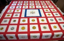"Image of 1977.136 - San Mateo Bicentennial Quilt, 1977. Machine pieced and hand-quilted cotton blanket shows a design of white squares with red sashing and a red outer border. A large blue-bordered square at center shows the Great Seal of the United States with an eagle, the phrase ""e pluribus unum"", and stars. ""SAN MATEO"" is hand-embroidered in gold thread at top in the blue border and ""CALIFORNIA"" is embroidered at bottom. To the left and right of the blue border is a white rectangle. The left-hand rectangle is hand-embroidered in gold with ""1776"" and ""1976"" appears to the right. Surrounding the emblem are white squares, each approx. 9.75"" x 9.75"" separated by red sashing. Copies of U. S. state seals, ranging between 3.5"" to 4.5"" in diameter, are hand-embroidered at the center of each white block. Background colors for state seals, if not white, are colored onto the fabric with paint or ink. 