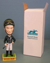 "Image of 2014.027.006 - Russell Baze Commemorative Bobblehead, 2006. Bobblehead (A) comes with box (B). Polychrome painted plaster base and plastic body shows jockey Russell Baze. The base is yellow with green on the top to represent grass. On the front of the base ""RUSSELL BAZE"" is visible and ""Bay Meadows"" appears on the back. The figure is standing with his feet apart and is wearing black boots, white pants, a long sleeve green top that has white cuffs, a white collar and a white bow tie. His left arm is bent with his fist placed on his hip. His right arm is slightly bent holding a black riding crop in his hand. His head is oversized compared to his body. The figure is smiling and has brown hair. He is wearing a green helmet with goggles resting on the brim. The helmet has a chin strap attached under the figure's chin. The head is attached to the body by a spring so that the head moves back and forth with vibration. The front of the jacket is signed with ""Russell  /  Baze"" in silver ink with cursive script. ""Baze"" is smeared. On the right side of the helmet, ""Russell  /  Baze"" also appears in silver ink. There is paper label adhered to the bottom that reads, ""WORLD  /  PROMTIONAL PRODUCTS, INC.  /  949-221-0690  /  Made in China."" ""WORLD"" has a compass graphic for the 'O'.