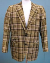 "Image of 2014.029.001 - Sport Coat Worn by Bing Crosby, c. 1959 - 1977. Plaid jacket predominately green with white yellow, purple, and black colors integrated into the pattern. Jacket has a wide collar.  Two gray buttons hold the jacket shut. On the right towards the center are two pockets. Top pocket is 4"" wide with a 2"" flap. Pocket below is 6"" long with no flap. On the left side towards the top is a 4"" pocket. On the bottom left is a 6"" pocket. At the end of each sleeve are two small gray buttons. The jacket is partially lined with a grayish-brown material with a satin finish. The inside of the sleeves is lined in a white fabric with a satin finish. Towards the top of the coat interior near the collar is a white label with blue text that reads, ""BING CROSBY."" On the inside right there is a 6"" pocket. Below the pocket is a black patch with embroidered cursive white writing that reads, ""Tony DeGrandis  /  INC."" Around the patch is white stitching. The back of the jacket has a 12.5"" slit. Jacket shoulders are padded."