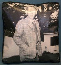 """Image of 2014.029.007 - Autographed Bing Crosby Vinyl Pillow, n.d. Rectangular pillow has a black and white photograph of Bing Crosby printed on vinyl fabric on the front side with glossy vinyl fabric on the back and sides. The black fabric has a pattern of creases running through it. The sides of the pillow are an inch and a half deep. The photograph on the front shows Bing Crosby in three quarter profile with his face turned toward the camera. He is wearing a plaid jacket with white buttoned down shirt, tie, and pants. He is wearing a white brimmed hat with a black band. His right arm is visible with the hand inside the pocket. He is standing outdoors with a building and a large tree in the background. The pillow is signed in the center with blue ink that reads, """"To Priscella  /  Yours  /  Bing  /  Crosby."""""""