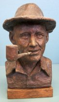 "Image of 2014.029.009 - Portrait Bust of Bing Crosby by Dutch Bieber, 1976. Portrait bust ends at shoulders with no arms visible. Figure is wearing a collared shirt. Figure is shown with a pipe in his mouth that protrudes out to the right side. Towards the figure's mouth the pipe is missing plaster and structural wire is exposed. Figure is wearing a flat topped hat with a 2"" brim. Plaster is painted a brownish-bronze color. Hair is carved into the sculpture. Statue is mounted on rectangular wood base."