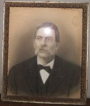 """Image of 2015.035.002 - Framed Portrait Drawing of Francisco """"Chico"""" Gonzales, 1902. Black and white chalk drawing on tan paper of Francisco """"Chico"""" Gonzales, son of the grantee to Rancho Pescadero, Juan Gonzales. The image shows an older man wearing a dark suit and vest, white button down shirt, and black bow tie. The man faces forward with his head turned slightly to his right, looking into the distance. The man has short salt and pepper hair that is combed over to the right side of his head. His mustache shows whiskers that extend down to his his jaw line on the sides. The pastel drawing is held in a wood frame that has smooth outer edges and dimensional floral and geometric motifs on the interior edge."""