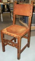 Image of 2015.037.018 - Spanish Side Chair, c. 1825-1875.  Chair constructed with medium brown walnut wood and similarly colored leather seat and back rest. The leather is held in place with upholstery tacks that have a large dome head. A small rectangular piece is cut out of the leather at each corner of the seat, so that the leather wraps down over the apron of the chair seat on each side. The leather seat is held in place with six tacks on each side. On the chair back, leather is stretched across the top and cross rail in a similar fashion to the seat. The leather on the back is attached with four tacks on the front and side of each stile and six tacks each on the top side of the top rail and the underside of the cross rail. The front stretcher is carved with geometric designs and the chair ears are carved into scroll shapes.