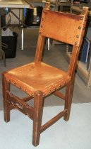 Image of 2015.037.019 - Spanish Side Chair, c. 1825-1875.  Chair constructed with medium brown walnut wood and similarly colored leather seat and back rest. The leather is held in place with upholstery tacks that have a large dome head. A small rectangular piece is cut out of the leather at each corner of the seat, so that the leather wraps down over the apron of the chair seat on each side. The leather seat is held in place with six tacks on each side. On the chair back, leather is stretched across the top and cross rail in a similar fashion to the seat. The leather on the back is attached with three tacks on the front and side of each stile and five tacks each on the top side of the top rail and the underside of the cross rail. The front stretcher is carved with geometric designs and the chair ears are carved into scroll shapes.