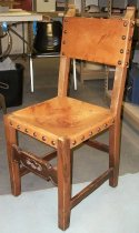 Image of 2015.037.020 - Spanish Side Chair, c. 1825-1875.  Chair constructed with medium brown walnut wood and similarly colored leather seat and back rest. The leather is held in place with upholstery tacks that have a large dome head. A small rectangular piece is cut out of the leather at each corner of the seat, so that the leather wraps down over the apron of the chair seat on each side. The leather seat is held in place with six tacks on each side. On the chair back, leather is stretched across the top and cross rail in a similar fashion to the seat. The leather on the back is attached with four tacks on the front and side of each stile and six tacks each on the top side of the top rail and the underside of the cross rail. The front stretcher is carved with geometric designs and the chair ears are carved into scroll shapes.