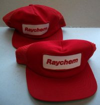 "Image of 2016.001.054B - Raychem New Era Baseball Caps, c. 1957-1999. Two red hats in a baseball cap style. The bill is rigid and covered in red and green fabric. The red fabric is stitched to the top with red thread. The underside of the bill is covered in green fabric and stitched on with green thread. The hat dome is comprised of five triangular panels sewn together. The front panel is the largest and is yellowish foam covered in red fabric. In the center of the panel is a patch. The patch is rectangular with rounded corners. The patch is white fabric with a red stitched boarder and ""Raychem"" embroidered in red in the center. The four remaining panels are red plastic mesh. The two back panels have a semi-circle cut-out. At the base of the semi-circle are two red plastic strips. Both strips have rounded ends. One strip has seven plastic pegs down the center. The other strip has seven holes. The pegs fit in the holes. On the inside, along the bottom edge of the dome is a black strip of fabric attached with black thread. Held between the seam of the black strip and red mesh is a white fabric tag. The tag has text printed in red ink and identifies it as a New Era brand hat. On the inside, three thinner strips of black fabric are sewn along the edges of the panels. Where the thin black strips meet is a round metal disk. On the outside, at the very top of the dome is a round button covered in red fabric."