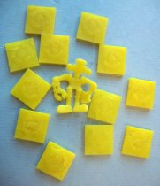 "Image of 2016.001.003A-B - Robot ""A Strange Change Toy"" Capsules, late 1960s to 1970s. Thirteen yellow ""time capsule"" pieces made of irradiated plastic produced by the Raychem Corporation as part of ""A Strange Change Toy Featuring the Lost World."" The toy set was sold by Mattel, Inc., and also included a machine with a heated dome and a compressor device, tweezers, instructions, a 3-D molded plastic ""Lost World Landscape,"" and an illustrated map. The square capsules expand into toy figures when heated. They can also be re-compressed back into squares and expanded again. The robot figure (a) has a head, two arms and two legs. The head has rounded edges and hash marks pressed into the front with a circular mouth. The main portion of the head is rectangular with an oval at top and flat circles at right and left. The lower part of the right arm is shaped like a shovel and the lower part of the left arm is shaped like a mechanical claw. The square chest is embossed with undetermined design. The feet are embossed with little dots. Twelve compressed square capsules (b-m) are embossed with Mattel's logo. The other side also has a Mattel logo and a pressed circle to the bottom left of the logo with a number embossed in the center.  The numbers range in 50s, 60s and 70s."