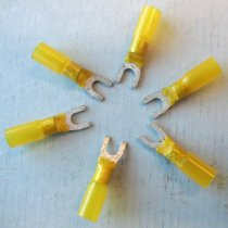 Image of 2016.001.011 - Raychem Yellow Fork Terminals, c. 1957-1999. Each of the six terminals have a metal fork-shaped piece. The metal piece forms a ring at its base. The yellow nylon Duraseal plastic covers a portion of the fork and the entirety of the metal ring. Yellow glue can be seen coming up from the tubing onto the metal fork.