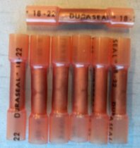 Image of 2016.001.015 - Raychem Orange Duraseal Wire Splices, c. 1957-1999. Seven orange Duraseal couplings. Couplings are made of nylon and tube shaped. Tube pinches in the middle to seal around copper alloy tube. A circular hole divot in the metal tube can be seen through the translucent nylon tube.