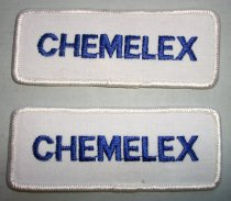 "Image of 2016.001.020A-B - Chemelex Patches, c. 1969-1999. Two white rectangularly patches with rounded edges. Thicker, outer stitching is also white. ""CHEMELEX"" is embroidered with blue thread in patch's center. Back of patch has appliqué coating. One patch has thread ends taped down with small piece of masking tape."