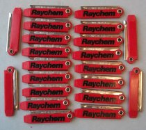 "Image of 2016.001.021 - Raychem Boxcutter, c. 1957-1999. Twenty-one red box cutters. The red plastic body is rectangular in shape with one end tapering slightly. The plastic is textured in a wood grain-like pattern. On one side ""Raychem"" is pressed into the plastic and painted black. The upper right corner of the body is molded into a plastic circle in which a metal arm is attached. Mounted in the arm is a metal blade shaped like a rhomboid. The arm and blade fold back into the red plastic body."