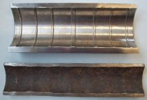 Image of 2016.001.043A-B - Raychem Large Coupling Pieces, c. 1957-1999. Two metal alloy pipes. Both pipes have been cut to exposed the interior. The exterior half pipe (A) is missing a little over half. It has a smooth outside. The inside has seven ribs evenly spaced. The very center rib is slightly wider. The removable interior pipe (B) is probably cut to be a third of it's original size. The outside has indentations which match up to the ribs on the exterior pipe (A). This piece is heavily rusted and oxidized. The interior pipe fits in the exterior pipe, but the interior pipe is longer by half an inch on one side and a quarter inch on the other side.