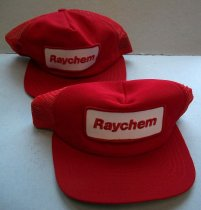 "Image of 2016.001.054A - Raychem New Era Baseball Caps, c. 1957-1999. Two red hats in a baseball cap style. The bill is rigid and covered in red and green fabric. The red fabric is stitched to the top with red thread. The underside of the bill is covered in green fabric and stitched on with green thread. The hat dome is comprised of five triangular panels sewn together. The front panel is the largest and is yellowish foam covered in red fabric. In the center of the panel is a patch. The patch is rectangular with rounded corners. The patch is white fabric with a red stitched boarder and ""Raychem"" embroidered in red in the center. The four remaining panels are red plastic mesh. The two back panels have a semi-circle cut-out. At the base of the semi-circle are two red plastic strips. Both strips have rounded ends. One strip has seven plastic pegs down the center. The other strip has seven holes. The pegs fit in the holes. On the inside, along the bottom edge of the dome is a black strip of fabric attached with black thread. Held between the seam of the black strip and red mesh is a white fabric tag. The tag has text printed in red ink and identifies it as a New Era brand hat. On the inside, three thinner strips of black fabric are sewn along the edges of the panels. Where the thin black strips meet is a round metal disk. On the outside, at the very top of the dome is a round button covered in red fabric."