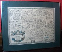 "Image of 2016.001.048 - Raychem Empire Map, 1978. Framed map of imaginary land. Map is printed in black and blue ink on cream colored paper. Small black Fleur-de-lys are printed along the edge as a border. Below that is a secondary border of black lines and light blue ovals. In each corner is a shield with a crown. A larger version of the crown and shield is placed in the middle of the bottom border. In the lower left corner, is a black and blue emblem of two people sitting on either side of a sun design. The figure on the left is a woman holding a sword. The figure on the right is a bearded man with his hand resting on a staff. The emblem also has scrolls and draped fabric. Below the sun is text explaining the map to be of the ""Raychem Empire"" and includes the name of the engraver. The main body of the map illustrates trees, mountains, buildings, power lines and fields. Areas of the map are labeled with names like: ""ENERGYLAND"", ""COUNTY OF CHEMELEX"", ""ELECTRONICKSBURG"" and ""TELECOMSHIRE"". The map matted with green matte board which is 2.75 inches thick. The frame is a brass-colored metal and has glass plate. The back is white cardboard. A wire for hanging is screwed onto the frame horizontally."