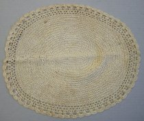 Image of 0002.231.002 - Dresser Scarf, n.d. Light tan oval crocheted dresser scarf that is 11.125in. tall x 13.5in. wide. The majority of the doily is a repeating ring of stitches in an oval pattern. There is a visible line on the right side where the rows are connected to each other but all the rows on the left side are seamless. At 4.5in. out from the center there are three rows of open work crochet. These three rows are 0.75in. wide. The last row is 0.5in. wide scalloped crochet stitch.