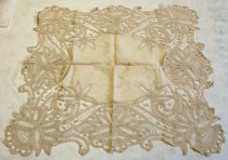Image of 1976.067A - Lace Table Cover, n.d. Rectangular 27in x 26in. Creme colored. The cover consists of one solid linen center piece appoximately 12.5in x 11.5in surrounded by a floral motif cut work detailing; the cut work overlaps the corners of the linen center so from the sides of the linen to the sides of the cut work is 7in. and from the corners of the linen to the corners of cutwork is approximately 13in.