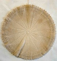 Image of 1976.067B - Crocheted Hot Plate Cover, n.d. 8in. diameter, 25in. circumference. Creme in color, hand-crocheted. 0.25in opening in the center (circular). 16 open dotted lines extend from the center to the edges. 16 triangular shapes made using a tighter crochet method extend from the center towards the edge. Edge consists of scalloped look made from evenly places knots 0.25in apart. On the bottom there is a 0.75in lip which held the cover in place. A string runs through the lip meeting at on point in the circle and creating a knot. (used as a tightening method)