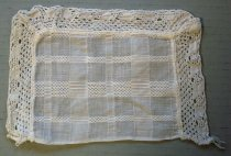Image of 1976.300.014 - Doily, n.d. Off-white rectangular doily with crocheted lace trim. The trim is only attached to the top, left and right sides. The fabric is a plaid pattern consisting of 7 rows and 10 columns of pattern stitched and solid fabrics. The trim is hand crocheted and attached. The doily is approximately 4.875in. tall x 6.875in. wide. The lace trim extends 0.875in. from the edge of the center panel which is 4in. x 5.125in.