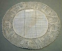 Image of 1979.073.002B - Circular Round Doily, n.d. Ivory in color. Consists of a smaller 3.25in diameter circle of linen surrounded by 1in. of handmade lace edging. The center circle has two lines going across the height and two lines going across the width to create 9 sections. The lace consists of tighter and looser woven threads creating an organic repetitive pattern.