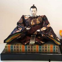 """Image of 2016.007.001 - Japanese Emperor Dairi-hina Girl's Day Doll, n.d.  Emperor dairi-hina doll (A) that sits atop a Japanese Girls' Day display during Hina Matsuri """"Festival of the hina dolls.""""  Made in Japan.  Male figure has white porcelain head and white plastic hands and feet.  His short black hair is secured in a top-knot with brown cordage.  He is wearing a brown and black robe printed with white birds (?) with orange and golden details.  Figure has very broad shoulders.  The sleeves and neck of his robe is lined with layers of gold, green, violet and white fabric.  There is a white with black edges 3"""" wide 'mat' strapped to the figure's back with a black leather belt.  Bottom of doll is shaped like an oval with pointed ends and is wrapped in a white-on-white checkerboard fabric with decorated with round medallions.  Front of this 'oval-shaped' pad has overlapping 'legs' from which extend white plastic feet.  Accessories included with doll are sword w/sheath, helmet w/separate black screen rectangular decoration and a wooden stick. Also includes two bases: larger bottom base (B) is painted solid black lacquer along outer edges while smaller top base (C) is covered in sewn plant material with fabric-lined edges front and back.  The top edge of front and back has a striped green, tan, blue, brown, indigo and orange motif printed with diamonds.  This wraps around corner to side edges which are also covered in the sewn plant fiber.  Front of base has matching printed fabric while fabric on back is solid red."""