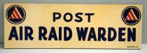 """Image of 0000.752.035A - Air Raid Warden Sign, n.d. This wooden sign is rectangular in shape, with a beige background with blue and white circles on the left and right of the sign and some unfinished wood in the back. Within each of these blue and white circles is a white/red striped triangle, which represents the symbols for Air Raid Wardens under the United States Citizen Defense Corps. In the middle of these circles, there is a text painted in blue and bold, all in uppercase that reads """"POST / AIR RAID WARDEN"""". At the far bottom right corner of the sign is an insignia that reads """"WILMES"""", which is in text painted smaller than the words """"POST / AIR RAID WARDEN"""" above."""