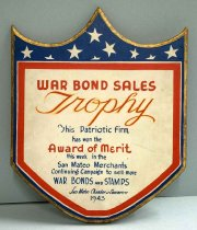 "Image of 0001.105 - War Bond Plaque, 1943. This plaque is made of wood and is painted white with a red border and blue background with white stars on the top.  It is shaped like a shield with two scallops with three tips. It has a gold outer border around the shield with wooden varnish at the back of the plaque. Within the red border of the plaque, there is a block of text painted in red, blue and gold. Written in red and in bold, the text reads ""WAR BOND SALES... / AWARD OF MERIT"".  The text ""WAR BOND SALES"", the ""A"" in the word ""AWARD"" and ""M"" in the word ""MERIT"" are upper cased.  Written in red and gold and in italics, the text reads ""TROPHY"". ""T""in the word ""TROPHY"" is upper cased and the rest of the letters are lower cased.  The gold lettering is painted around the word ""TROPHY"" that is already painted in red. Written in blue, the text reads ""THIS PATRIOTIC FIRM... / HAS NOW THE... / THIS WEEK  / IN THE / SAN MATEO / MERCHANTS / CONTINUING CAMPAIGN TO SELL MORE  / WAR BONDS AND STAMPS / SAN MATEO CHAMBER OF COMMERCE / 1943"". The words ""T"" in the phrase ""THIS PATRIOTIC FIRM"", ""S"" and ""M"" in the words ""SAN MATEO"" and MERCHANTS"", and ""C"" in the phrase ""CONTINUING CAMPAIGN"" are upper cased in regular font. The ""H"", ""N"" and ""T"" in the phrase ""HAS NOW THE"", and the ""T"", ""W"", and ""I"" in the phrase ""THIS WEEK IN THE"" are lower cased in regular font. The words ""WAR BONDS AND STAMPS"" is in bold except for the word ""AND"" which is in small lettering. The words ""SAN MATEO CHAMBER OF COMMERCE"" are italicized, but also smaller than the rest of the text above. At the end of this block of text, the date ""1943"" is listed, which is also in regular font. At the back of the plaque, it has a wooden varnish with two small metal eye-screws. The two small metal eye-screws are connected to one knotted cotton string used for hanging onto a wall. Also on the back of the wooden plaque is a black iron metal latch with three tiny black screws."