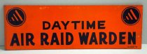 "Image of 1975.053 - Air Raid Warden Sign, n.d. This sign is rectangular in shape with a orange painted background containing  two black and orange circles. Within these two black and orange circles, they include a black/orange triangle, which symbolizes the insignia for the Air Raid Wardens under the United States Citizen Defense Corps. In the middle of the sign, painted in black, and written in bold, the text reads ""DAYTIME / AIR RAID WARDEN"". At the lower right hand bottom of the sign, the text reads ""WILMES"". The word ""WILMES"" is smaller than the rest of the text above and is also is black. Next to the word ""WILMES"" is an insignia shaped with like an oval, and is also painted in black. At the back of the sign, the wood is painted in a black background with some text in it. The text reads""...FO... / MEMBER... / ...ALTY... / ...SSOC... / ...GEARY... / ...BAYVIEW... "" The text appears to be engraved into the black painted background and is uppercased."