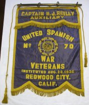 "Image of 1983.203 - Captain H. J. Reilly Auxilliary United Spanish War Veterans Banner, 1926. Satin banner with decorative trim hangs from a brass-colored pole. The front of the banner is constructed with blue satin that is machine embroidered in a chain stitch with gold-colored lettering. Gold-colored trim that is 1"" wide is sewn around the edges and 1.75"" long twisted fringe hangs down from the bottom edge. The banner has a 11"" x 29.5"" satin flap attached to the top that has a scalloped lower edge. This piece is also decorated with gold-colored trim and fringe.  Text on the banner from top to bottom reads, ""CAPTAIN H. J. REILLY  /  AUXILIARY  /  UNITED SPANISH  /  WAR VETERANS  /  INSTITUTED AUG. 28, 1926  /  REDWOOD CITY.  /  CALIF."" An embroidered emblem in the center of the banner shows a white cross with yellow edging within a circular wreath of gold-colored leaves. A red star with eight points appears behind the cross and the points extend over the border of leaves. Within the cross, ""NATIONAL * AUXILIARY  /  * U. S. W. V. * is embroidered with gold-colored thread inside a circular border that frames an image of two soldiers in a landscape who are holding rifles and stand on either side of a kneeling a female figure.  The back of the banner is lined with green satin. The banner is sewn to four metal rings along the top edge, and a metal pole with a wooden core slides through the metal rings for hanging. A gold-colored cord is tied to the two outer rings at the top of the banner and hangs down on either side. Each end of the cord has a large gold-colored 1.25"" diameter tassel."