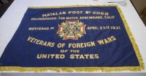 "Image of 1983.205 - Veterans of Foreign Wars Flag, n.d. Rectangular dark blue banner with gold lettering and the United States eagle emblem in the center. The top right and bottom edges have gold tassels attached. The gold lettering is machine done in a satin stitch. The blue fabric is similar to a silk. The words on the banner say ""MATALAN POST NO. 2068 / HILLSBOROUGH, SAN MATEO, BURLINGAME, CALIF / MUSTERED IN APRIL 23RD 1931 / VETERANS OF FOREIGN WARS / OF THE / UNITED STATES"" The first line (""MATALAN POST NO. 2068"") is the largest font curving up in the center and the next two lines are medium font. The fourth line (""VETERANS OF FOREIGN WARS"") is also in the larger font but curving down in the center. The fifth line  (""OF THE"") is in smallest font and the sixth line (""UNITED STATES"") is in medium font. The left side of the banner has no fringe attached and has a loop where a pole could have been. The loop was originally machine stitched but it looks like over time it was hand stitched to stay together. The seal in the center is 17in. x 17in. it has 4 large identical geometric shaped extending up down and to the right and left of it. Their coloring starting from the inside is creme, gold, dark orange, gold. In between each of these 4 shapes is 3 smaller shapes which point towards the  4 corners of the banner. The three shapes are solid colors, the two on the outside are light orange while the third one in the center is gold. All of these shapes surround a circular banner with the words ""VETERANS OF FOREIGN WARS OF THE UNITED STATES"". Inside that circle is another circle with the United states seal with the eagle with wings spread, holding arrows in one talon and an olive branch in the other. There is a shield covering his chest with a blue rectangle on top and red and white vertical stripes on the bottom. Theres a gold banner behind its head with black font reading, ""E PLURIBUS UNUM"", and a 13 stars encircled above its head."