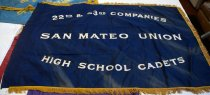 "Image of 0001.917.001-.002 - San Mateo Union High School Cadets Flag, n.d. Dark indigo blue flag is made of silk fabric, is rectangular in shape and has a gold 2"" cloth fringe, comprised of twisted cord, around the top, bottom and right sides.  Left side has a 2.875"" folded hem on back for inserting a flag pole.  Machine-embroidered on front (and visible from back) in white thread are two inch letters that read, ""22 nd. & 23 rd. COMPANIES  /  SAN MATEO UNION  /  HIGH SCHOOL CADETS.""  Center line of text is straight while top and bottom lines have a slight curve, arching around the center line."