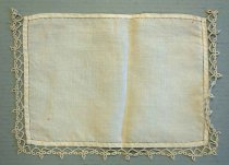Image of 0002.229.006 - Dresser Scarf, n.d. Rectangular creme table scarf with tatted lace on three sides. The lace is only on the left, right, and top sides.  The only decoration on the fabric is an inner border of hemstitching on each side that is a 0.25in in from the edge of the fabric panel. The tatted lace edging is attached to the curved edge only with hand stitching. The lace has a pattern of loops and circles.