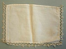 Image of 0002.229.007 - Dresser Scarf, n.d. Rectangular creme table scarf with tatted lace on three sides. The lace is only on the left, right, and top sides.  The only decoration on the fabric is an inner border of hemstitching on each side that is a 0.25in in from the edge of the fabric panel. The tatted lace edging is attached to the curved edge only with hand stitching. The lace has a pattern of loops and circles.
