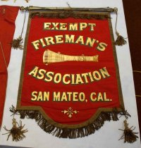 "Image of 1974.297 - Exempt Fireman's Association Banner, n.d.  Bright red cloth banner is rectangular in shape with an inverted arch section at bottom center.  Back is lined with a lighter red-colored fabric.  Front is bordered with a 1"" metallic bronze-colored ribbon.  Beneath ribbon along top edge is a 2"" bronze-colored metallic fringe.  A similar 2.25"" fringe is suspended just below bottom edge.  Suspended from the bottom two corners on 2.5"" cord are matching 5"" metallic tassels.  A 5.5"" x 14"" gold-colored horn is painted on the center front of the banner.  Above and below the horn in gold 3"" lettering that is shadowed by dark and light green is text that reads, ""EXEMPT  /  FIREMAN'S  /  ASSOCIATION"" and in 2.5"" lettering below that, ""SAN MATEO, CAL.""  In the center of the inverted arch section at bottom, painted in gold, is a decorative emblem consisting of four flowers that form a cross.  Affixed to top of banner are four brass rings through which a brass-colored metal dowel is threaded.  Ends of dowel are capped with round brass-colored metal 1.5"" finials.  Dowel has a center eye screw for hanging and two end eye screws through which a bronze-colored cord with three center loops is affixed."