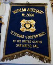 "Image of 1983.207 - Matalan Auxiliary No. 2068 VFW Banner, n.d. Rectangular cloth banner has an inversed V-shape at bottom.  Fabric is a dark marine blue on front with a turquoise blue backing.  Front edge is bordered with 1"" gold ribbon.  Painted in the center front is an emblem consisting of a white and yellow cross on a gold ground with a gold circle with an eagle in the center surrounded by a blue border on which is printed, ""AUXILIARY  /  V.F.W.""  Printed above emblem is gold 3"" text with a light blue shadow and light tan highlights that reads, ""MATALAN  AUXILIARY  /  No. 2068.""  Below emblem is similar 2"" text that reads, ""VETERANS of FOREIGN WARS  /  OF THE UNITED STATES  /  SAN MATEO, CAL.""  2.25"" bronze metallic fringe hangs from bottom of banner with matching 4"" tassels hanging from 2.25"" cords from both bottom corners.  Across top are four brass rings though which a gold painted wooden dowel is thread.  Dowel has an eye screw at center for hanging, as well as smaller eye screws at ends through which bronze colored cord with three loops at center is secured.  Loose brass finials in the shape of acorns secure to dowel ends."