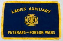 "Image of 1983.208.002 - Ladies Auxiliary V.F.W Banner, n.d. Rectangular royal blue banner with gold fringe stitched onto the edge. Silk/satin like fabric. The gold fringe extends 0.5in. from all 4 edges. In the center there is an emblem 3in. tall x 3in. wide. The emblem consists of an inner circle with the eagle symbol in the center and an outer circle with the words ""Auxiliary V.F.W"". Beyond that there are 4 rectangular shapes extending from the top, bottom, left,  and right. In between these are 4 different motifs, crossing swords, crossing anchors, crossing rifles and one unrecognizable. Above the emblem are yellow printed words reading ""LADIES AUXILIARY"" and below the emblem there are the words which read ""VETERANS OF FOREIGN WARS"" the lettering on the bottom is 0.75in tall and 10.375in wide. The lettering on the top is curved down at the ends making it 9in. across."