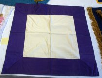 Image of 1983.209 - Matalan Post Ceremonial Table Cover, c. 1946-1981.  Square purple and off-white table cover. The table cover is all off-white with purple machine sewn onto the top edges. The purple frames an off-white center square 22 x 22in. The purple extends 5.875in. beyond the off-white square. The purple is only attached to the front. The back is all off-white.
