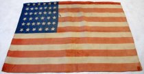 Image of 0000.274 - U.S. Flag, 1889. Silk fabric U.S. flag with 39 white stars on a blue ground and 13 red and white stripes. The stars are arranged in rows with the following counts from top to bottom: 6, 7, 7, 6, 7, 6. The edges of the flag are hemmed.