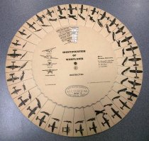 "Image of 0000.754.003 - Identification of Warplanes spotting wheel, April 21, 1942. This 12"" wheel is made of paper, and round in shape and is double sided. The wheel is connected to a round brown cardboard with black lines in between each photo of U.S. warplanes, which are all in shaded and drawn in black. Each of the planes is shown on its top and its side. The wheel is the middle of the round brown cardboard. It has edges all around the wheel, a small opening gap at the top and small brass hole in the middle of the wheel. Next to the small opening gap at the top of the wheel, there is some printed text in bold and black underneath columns of lines spaced out in between the text. The text reads ""WINGS AND LOCATION  /  NO. OF ENGINES  /  WING SHAPE FRONT  /  REAR  /  TIP  /  LANDING GEAR  /  TAIL AND RUDDER  /  NOSE  /  TYPE"". The words ""FRONT  /  REAR  /  TIP"" are disproportionately smaller than the rest of the text ""WING SHAPE"" and are on the same line as ""WING SHAPE"". The words ""NOSE  /  TYPE"" are on the same line. In the small opening gap, with a background in white on the round brown cardboard with a variety of black text underneath a column of lines that changes when spinning the spotting wheel. Below the text above and the small opening gap at the top, there is some more printed text in black and bold that reads ""IDENTIFICATION  /  OF  /  WARPLANES"". On the left of the text ""IDENTIFICATION OF WARPLANES"", there are some drawings of planes with some bold, black and tiny text below each picture of the plane that reads ""HIGH-WING  /  MIDWING  /  LOW-WING  /  PARASOL MONOPLANE"". In the middle of the wheel, below the small brass hole, in black, and bold with medium text, the printed text reads ""C"", which is surrounded by a small circle around it. Below the text above, in black and bold, the printed text reads ""RESTRICTED"". On the far right of the wheel, printed in black, the text reads ""KEY to  /  Descriptive Abbreviations  /  R.--Retractable Landing Gear  /  S.--Single Tail and Rudder.  /  B.--Blunt Nose.  /  L.--Long Nose"". The text ""R.--Retractable Landing Gear  /  S.--Single Tail and Rudder.  /  B.--Blunt Nose.  /  L.--Long Nose"" is in black with smaller lettering than the text ""KEY to  /  Descriptive Abbreviations. Below the drawings of planes and the text on the left, printed in black, bold with tiny lettering, the text reads ""[A. G. 452.9 (4-21-42)]"".  Across from the text above on the far right, printed in black, bold with tiny lettering, the text reads ""U.S. GOVERNMENT PRINTING OFFICE  :  1942--O-457035""."