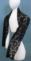 Image of 0001.631.002 - Scarf, n.d. Long black rectangular machine lace scarf with a repeating multi-petaled floral motif with connecting leaves, on a fishnet background.  Edges of scarf are cut in a slight scallop pattern and trimmed with a hand sewn decorative edge of tiny repeating loops.
