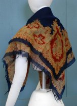 Image of 0001.943.001 - Shawl, n.d. Shawl made of silk? with dark blue fringe on each end. Dark blue background with a reddish, yellow, and blue floral motifs throughout and on each corner of the shawl.
