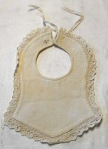 Image of 0002.300.012 - Baby Bib, n.d. Cream colored cotton bell shaped with lace edging. Main fabric has a diamond pattern on the front with white strings attached at the top. Soft texture on the back.