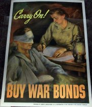 Image of 1982.150.003 - Carry On! Buy War Bonds Poster, 1943. This poster displays a woman sitting at her desk whike writing something on a piece of parchment while a man with bandages around his eyes and his right arm is laying down in a bed.