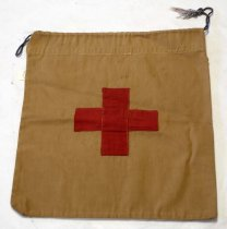 Image of 1997.066 - Red Cross Bag, n.d. Rectangular, brown canvas bag with stitched red cotton cross at center. The cross is comprised of two pieces of red fabric, stitched on top of each other. Top/opening of bag has a cinches closed with a pull-string made of cotton cordage that is blue.