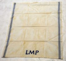 "Image of 1997.071.002 - Towel, Dish c. 1920s. White rectangular linen towel with three blue vertical lines on each side. At the bottom, center are three, blue embroidered initials ""LMP"". From Homestead/Hayward Park school c. 1920s. Brick is mounted on wood stand under plexi dome."