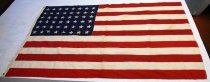 Image of 1999.083 - 48 Star United States Flag, c. 1890s. Flag is made of strips of fabric that are sewn together to create a striped pattern with red stripes on bottom and top edges. Upper right corner has blue section with 48 white stars printed on it.