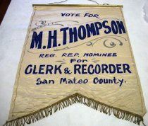 "Image of 2007.002 - M.H. Thompson Clerk & Recorder Election Banner, c. 1898. This banner is made of a cream-colored cloth with a dark golden fringe at the bottom. At the top, the banner is held up by a gold wooden pole with a golden string connected to the left and right of the gold wooden pole. There are gold pen marks around the inside of the banner with darker gray curves and lines in between the banner where the blue painted words say ""M.H. THOMPSON"". Inside of the gold pen marks around the cream colored banner, it has text painted in blue that says ""VOTE FOR  /  M.H. THOMPSON  /  REG. REP. NOMINEE  /  For  /  CLERK & RECORDER  /  San Mateo County."" The words ""M.H. THOMPSON"" shaped in blue around the words, and in black inside the words with golden specks on the ""M"", ""H"", ""T"", ""O"", ""S"", and ""N"" in ""M.H. THOMPSON"". The words ""M.H. THOMPSON"" are also disproportionately bigger than the rest of the words above. The words "" VOTE FOR"", ""REG. REP. NOMINEE"" , ""FOR"" , and ""San Mateo County."" are in regular font,  but smaller than the words ""M.H. THOMPSON"". At the bottom of the words ""San Mateo County."" underneath the middle of the gold pen border on the banner is some words that are spaced out and written in blue pen and in upper case that says ""E.P. EGAN 22 1/2 GEARY ST"". The cream-colored cloth banner appears to have a golden fringe which is stitched along the bottom of the banner."
