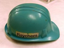 "Image of 2016.015.002.12 - Cam-Hi Safety Cap, 1973. Hard hat issued to Jim Thompson while working on the Trans-Alaska Pipeline project for the Raychem Corporation in 1975.  The hard hat has a blue molded plastic outer shell with a visor that is 2.25"" wide. The sides and back of the brim are upturned approximately 0.5"" for catching water and taper as the sides meet the visor in front. A small tab with a hole is molded on the right and left side of the shell for attaching strings to secure the hard hat in place on one's head. A rectangular 1.25"" x 4"" sticker with ""Raychem"" in black font on a gray background is adhered on the right and left side of the shell. The left side also has an oval sticker with red and black text on a clear background that reads, ""Raychem  /  PIPE PROTECTION  /  DIVISION."" ""Raychem"" is printed in red and ""Pipe Projection Division"" is printed in black.  On the front of the shell, ""Jim"" and ""Thompson"" are printed in black on two clear rectangular adhesive labels. An embossed vinyl adhesive label with ""THOMPSON"" in white font on a black background is adhered on the back center of the shell under a red and green sticker that reads, ""RAYCHEM  /  SAFETY IS NO ACCIDENT  /  MINE SPLICE KITS AND CABLE REPAIR SLEEVES."" The hat has an adjustable four point suspension made with plastic, cloth, and leather. The suspension protects the head so it is not in direct contact with the plastic shell. Leather is sewn over the front half of the headband, and the band has pinlock adjustment at the back. A brown cord can be tightened or loosened to adjust the tension of the suspension crown straps. A teletemp temperature sensing label is adhered on the interior of the shell on the left side, and a white sticker with specification information is adhered on the interior at the back. ""Cam-Hi Safety Cap  /  CH-69-C  /  MADE IN U.S.A."" is molded into the underside of the visor above a manufacturing date code of 1973 with unknown day and month markings.